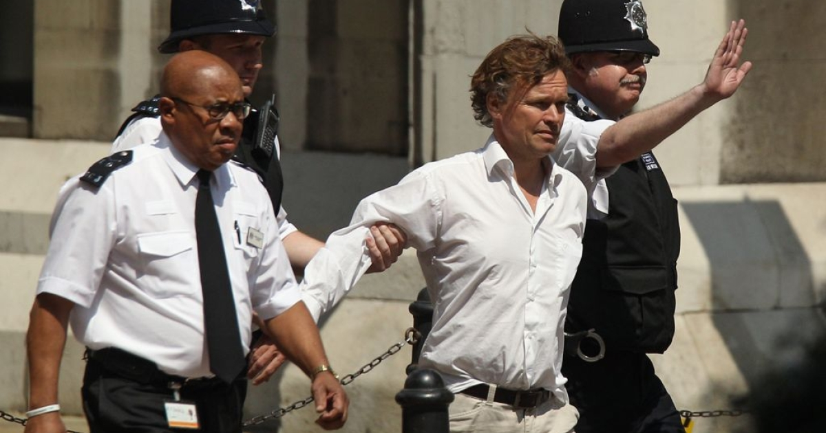David Lawley-Wakelin, who disrupted former Prime Minister Tony Blair's testimony at the Leveson Inquiry, is led away from the Royal Courts of Justice by police officers and security staff on May 28, 2012 in London, England.</p>