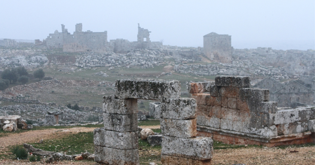 The ruins of the ancient city of Serjilla lay scattered across the mountains of Jabal al-Zawia. The isolated location of this ancient city has largely spared it from the bombardment of the inhabited villages, but some minor damage is still evident and the presence of refugee families that now live in the ruins further threatens the old Christian town.</p>