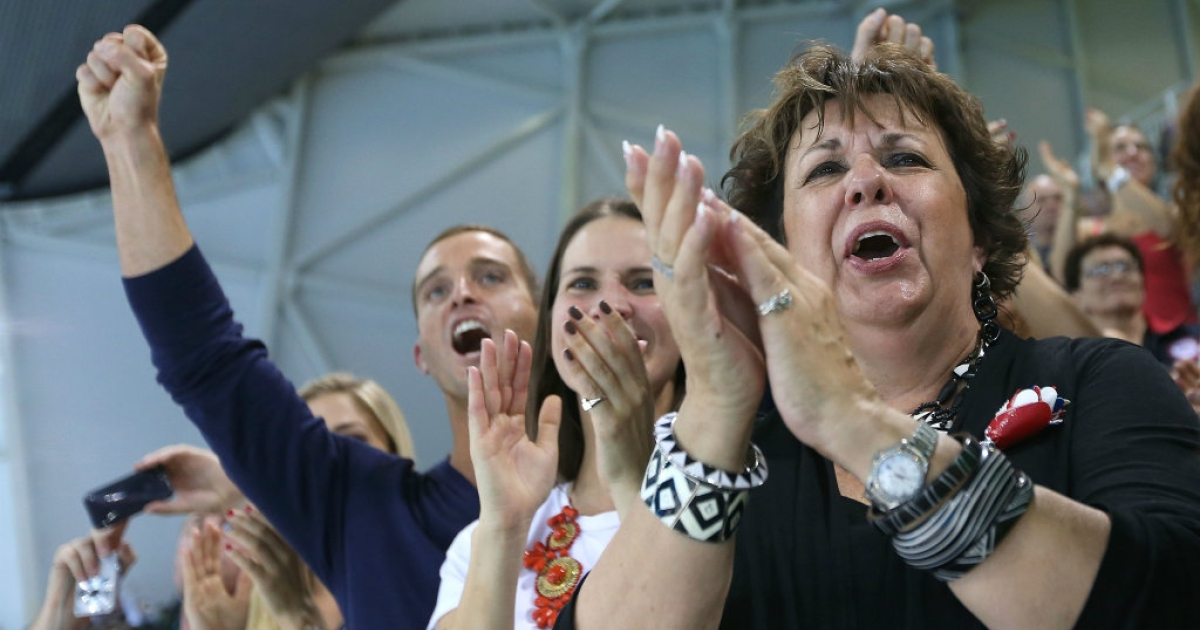 Michael Phelps's mother Debbie (R) and his sister Hilary (C) applaud as he receives his gold medal for the Men's 4 x 200m freestyle relay.</p>