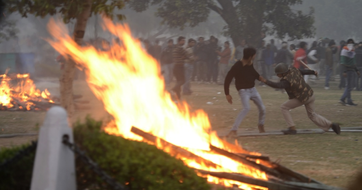 Indian police try to grab a demonstrator near burning barricades during a protest calling for  better safety for women following the rape of a student last week, in front the India Gate monument in New Delhi on December 23, 2012. In the biggest protest so far, several thousand college students rallied at the India Gate monument in the heart of the capital where they were baton-charged, water cannoned and tear gassed by the police.</p>