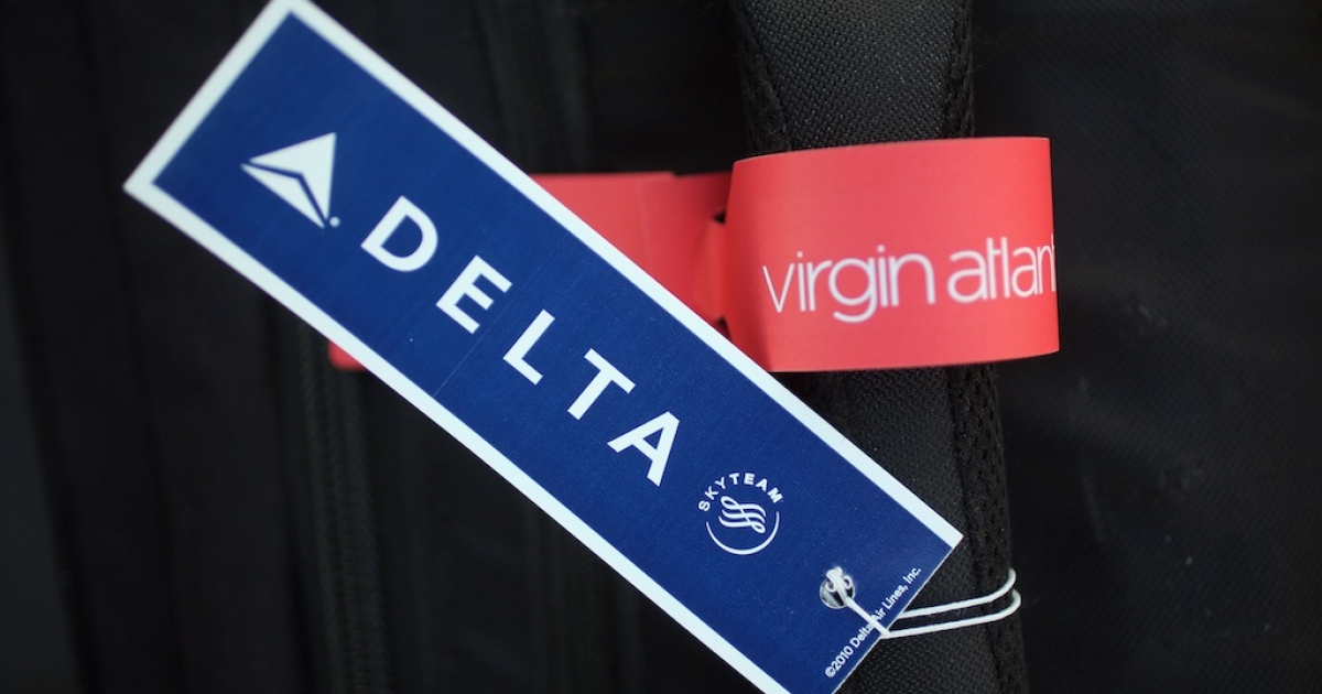 In this photograph illustration a Virgin Airlines and Delta Airlines baggage sit together on the handle of luggage on December 11, 2012 in Manchester, England. Delta Air Lines has agreed to invest $360m (£224m) to buy the 49% stake of Singapore Airlines in Virgin Atlantic. The airlines hope the new joint venture will create an expanded trans-Atlantic network.</p>