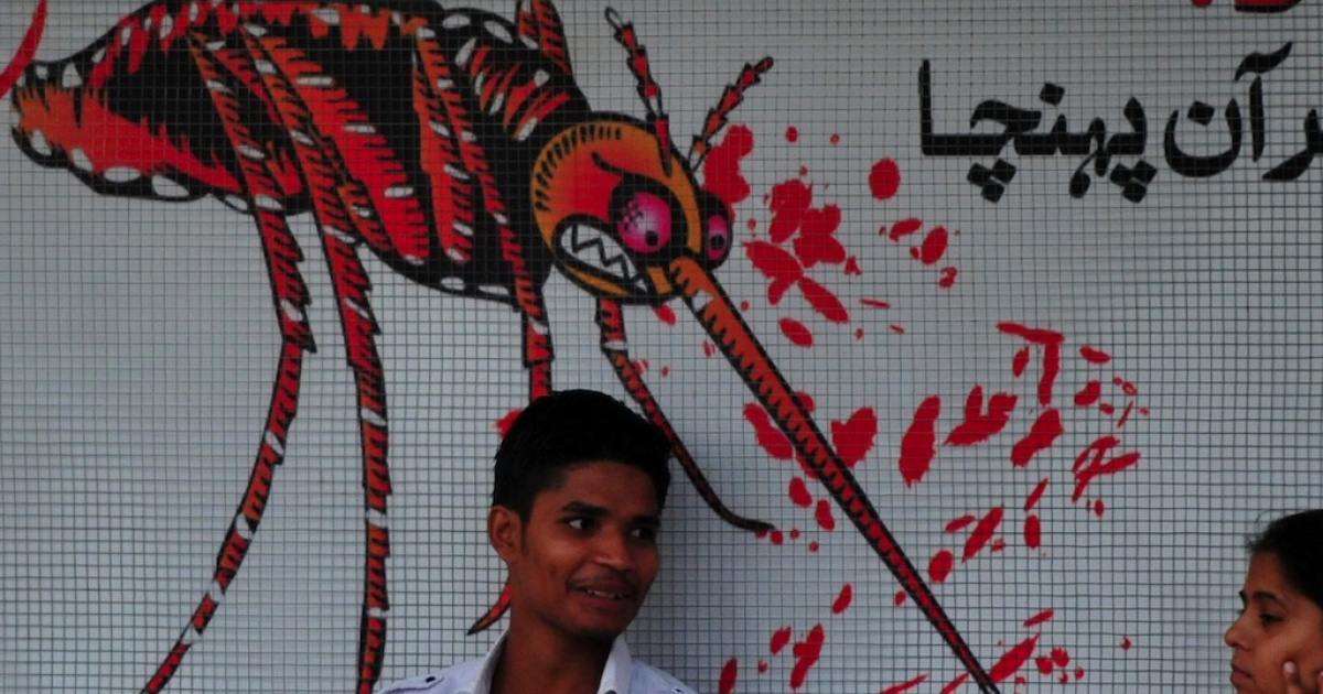 A Pakistani man sits in front of awareness advertisement against the dengue fever, a deadly tropical disease, in Islamabad</p>