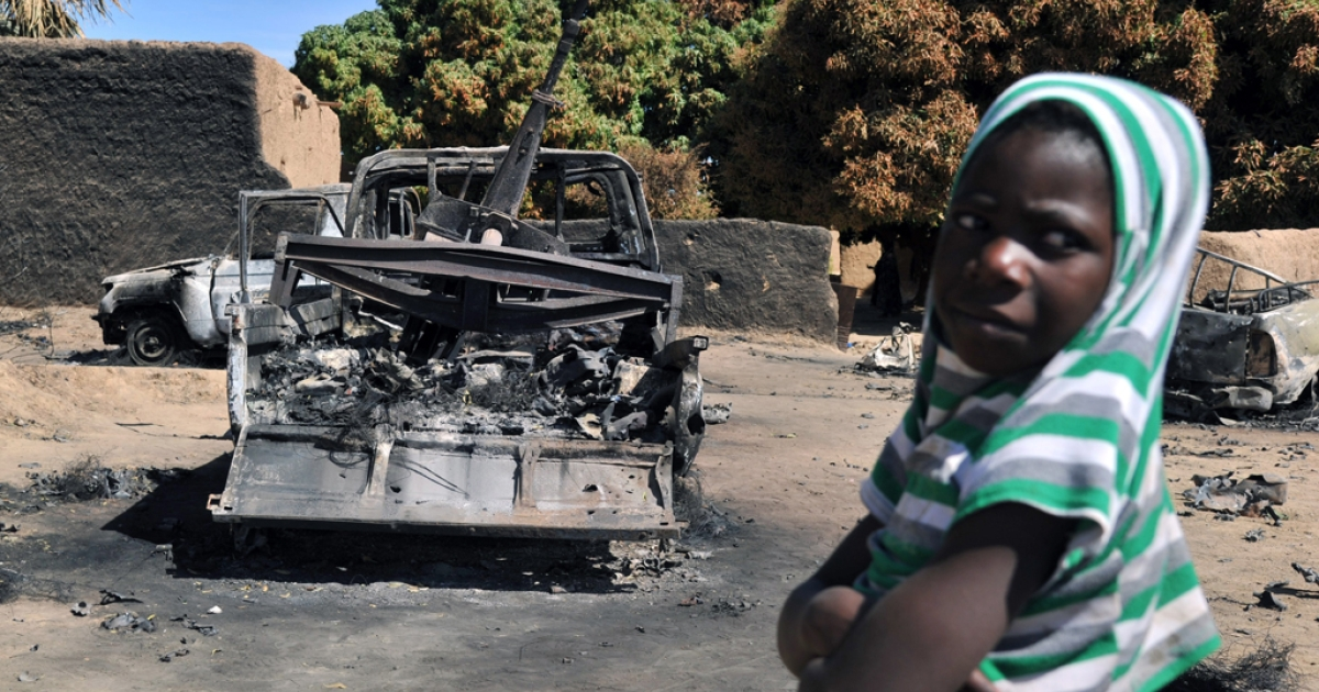 A boy stands next to a charred pickup truck on Jan. 21, 2013, in Diabaly — a town in the Ségou Region of Mali. Monday French and Malian troops recaptured the towns of Diabaly and Douentza from Islamist groups, ending a week-long series of air strikes and fighting that plagued the region.</p>