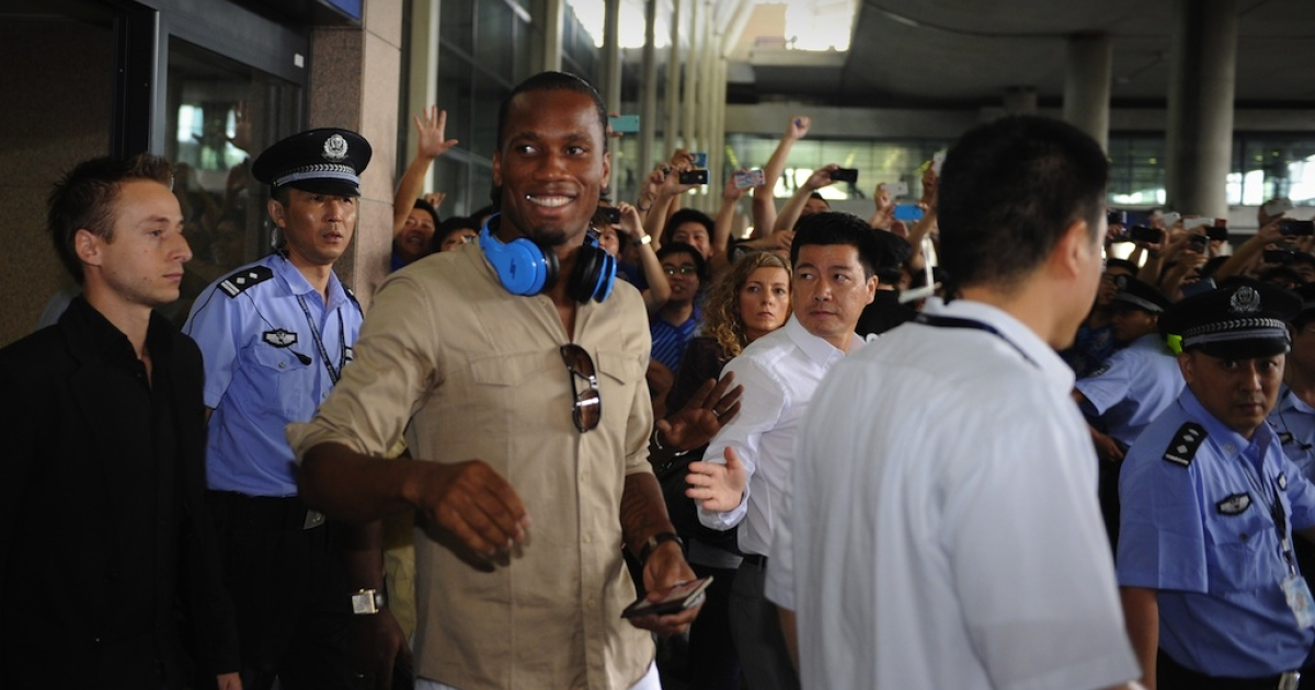 Fans greet Didier Drogba as he arrives at Shanghai Pudong International Airport.</p>