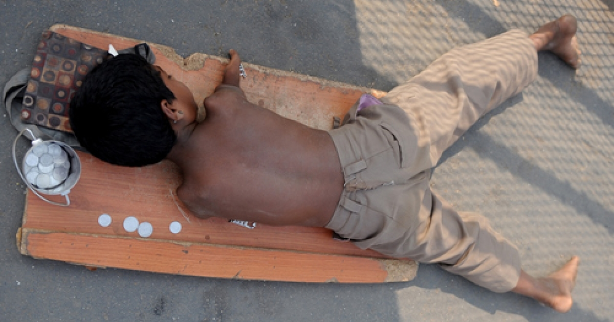 A handicapped child lies on a mat while begging for alms next to a few  Indian rupee and paise coins given to him in Mumbai on December 7, 2011. Rarely considered for conventional employment, there are few options for the disabled in India.</p>