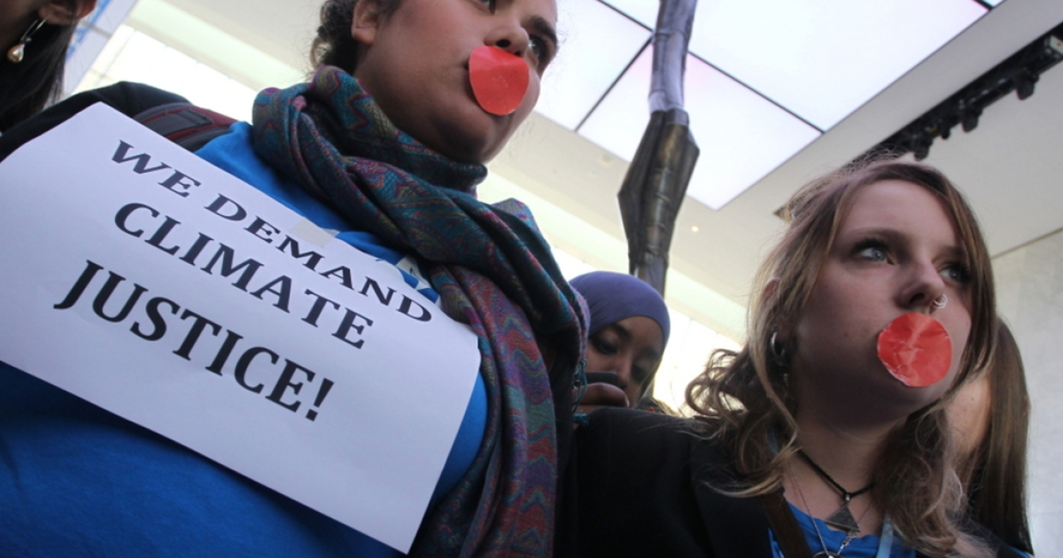 Activists march inside a conference center to demand urgent action on global warming at the UN climate talks in Doha, Qatar, on December 7, 2012.</p>