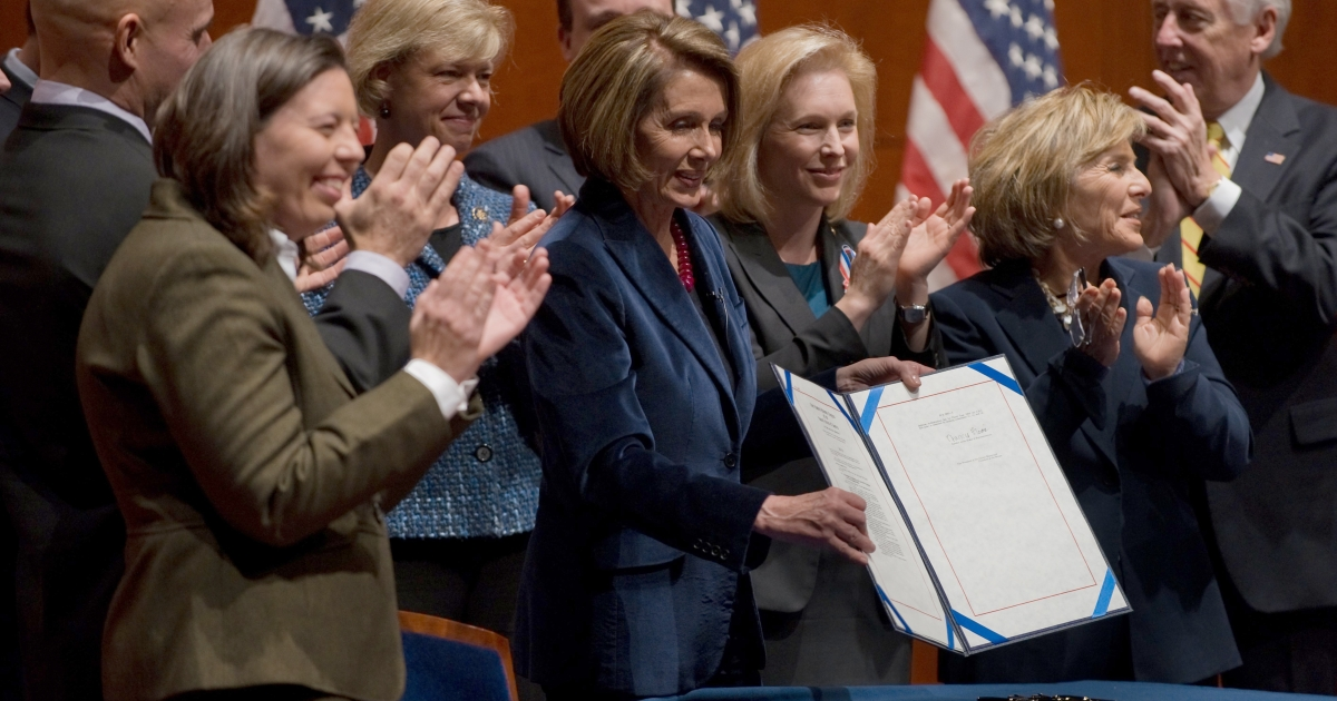 U.S. House Speaker Nancy Pelosi, surrounded by members of the House of Representatives, the Senate and three former members of the armed services who were discharged because of their sexual orientation, displays the repeal of the 'Don't Ask, Don't Tell' law after signing it on Dec. 21, 2010.</p>