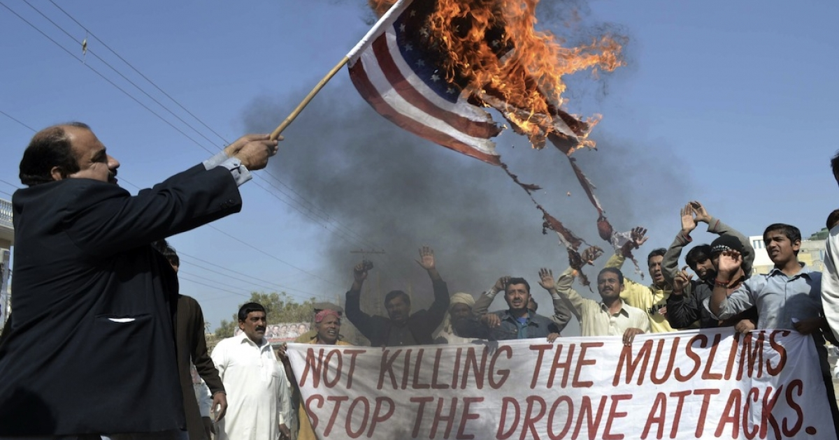 A Pakistani protester holds a burning US flag as they shout slogans during a protest in Multan on February 9, 2012 against the US drone attacks. Thousands have been killed by drones since 2004, many believed to be civilians.</p>