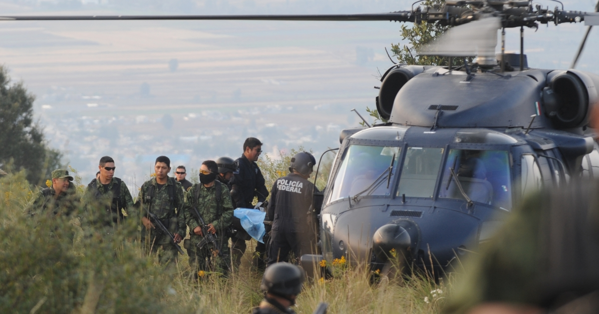 Members of the Mexican army and Federal Police remove the body of a victim following a helicopter crash that killed Mexican Interior Secretary Francisco Blake Mora on Nov 11 in Tlamanalco, Mexico state.</p>