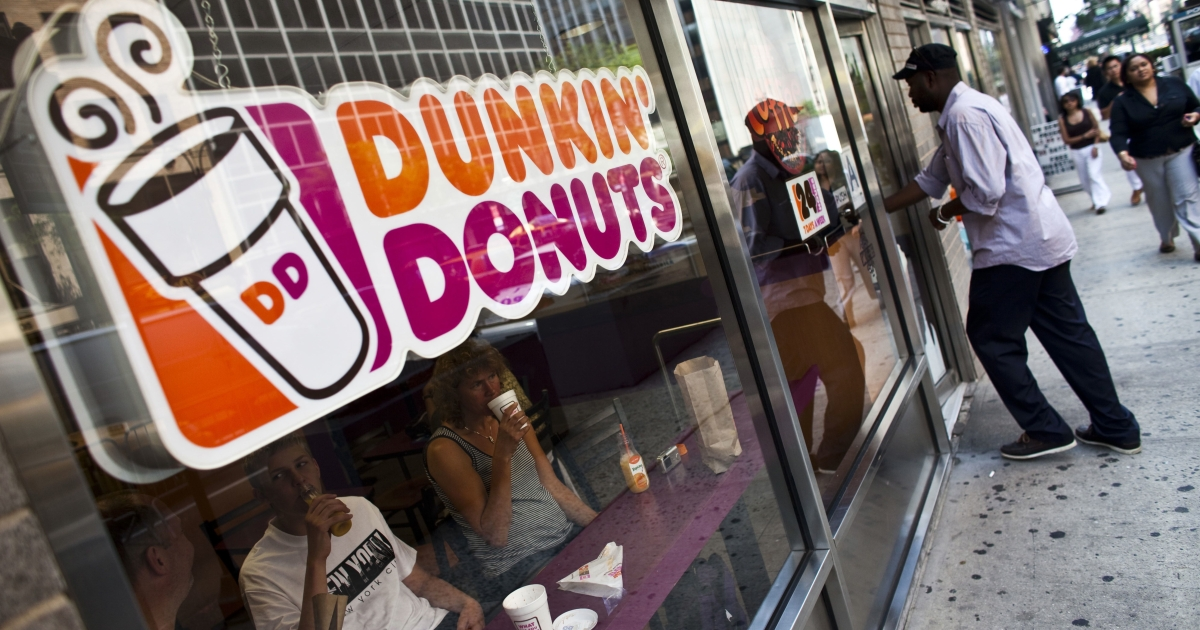 A man enters a Dunkin' Donuts store in New York.</p>