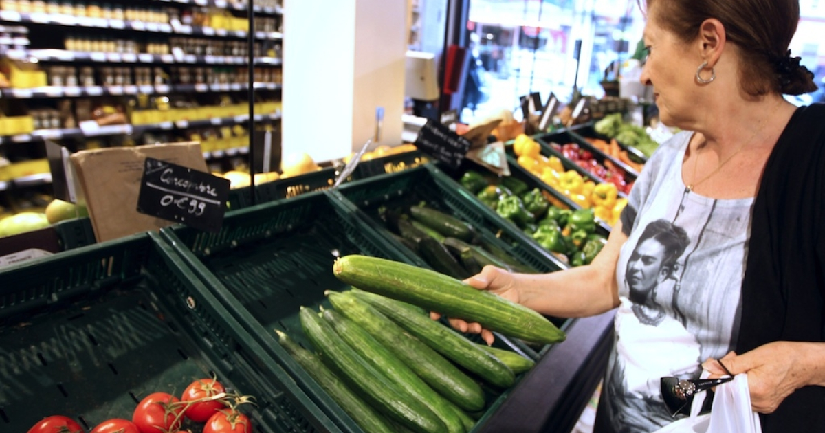 A woman picks up a cucumber from a vegetable stall on May 30, 2011, in a supermarket in Paris.</p>