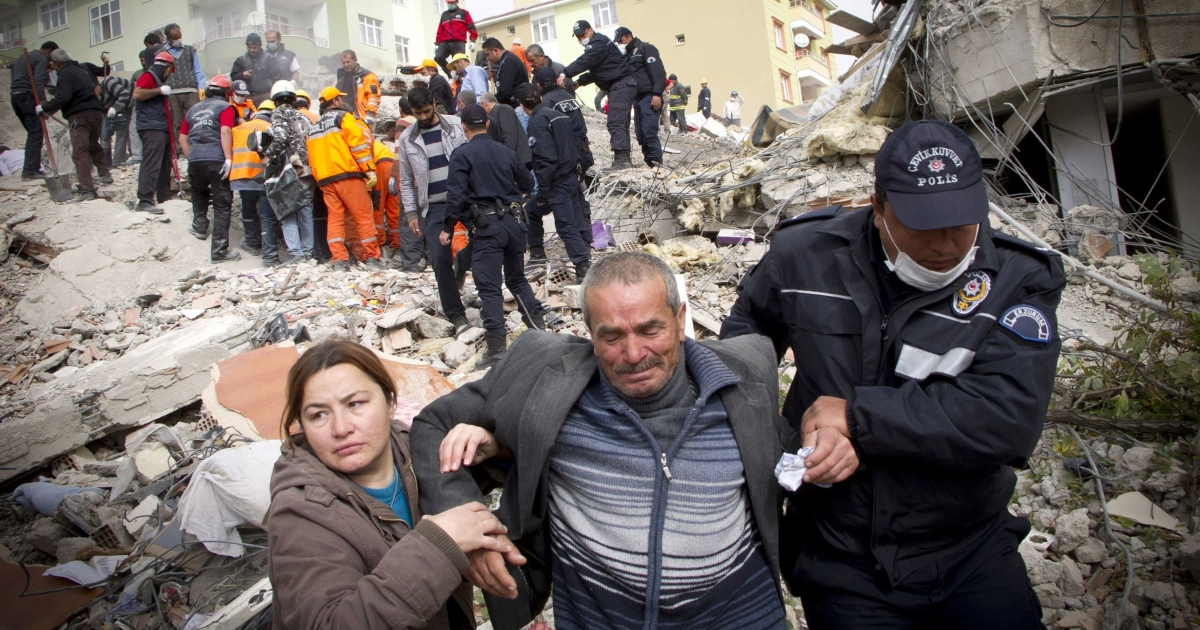 Relatives of victims cry on the ruins after an earthquake in Ercis province of Van, in Turkey, on Oct. 25, 2011.</p>