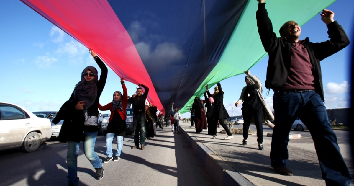 Libyans carry a flag, said to be 17 kilometres (10.5 miles) long and about three metres (nine feet) wide, from Tajura to Tripoli's Martyrs' Square on February 24, 2012 as Libyans continue to celebrate the first anniversary of the uprising that ousted Moamer Kadhafi.</p>