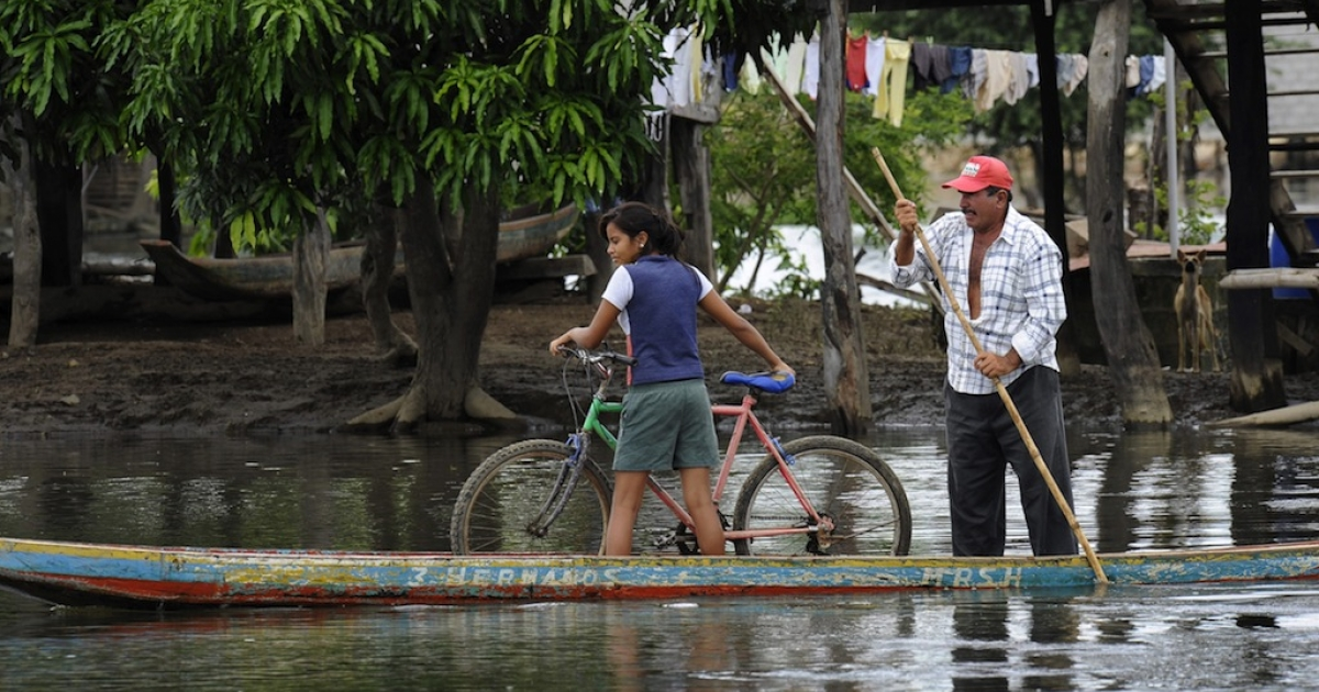A man transports a girl and her bike in a canoe through the floodwater on the outskirts of Salitre, 600 km southwest of the Ecuadorian capital Quito, on April 15, 2010.</p>