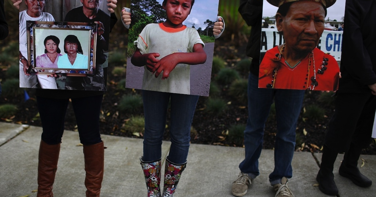 Protesters stand outside Chevron's US headquarters holding photos of Ecuadorian people affected by pollution in the Amazon on February 15, 2011.</p>