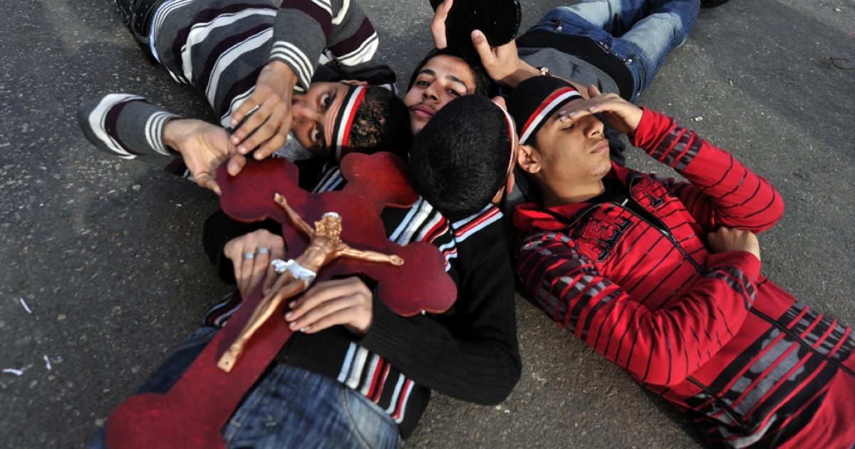Egyptian Coptic Christians lie on the ground while holding a cross during a protest outside the Egyptian state television building in Cairo on March 10, 2011. Sectarian clashes killed at least 13 people in Cairo this week, as old regime diehards attacked pro-democracy protesters in the biggest challenge yet to Egypt's new military rulers.</p>