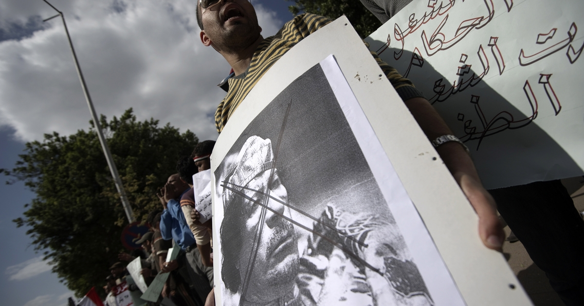 Protesters shout slogans against Libyan leader Muammar Gaddafi during a demonstration outside the Arab League headquarters in the Egyptian capital Cairo on Feb. 21, 2011 to condemn Libya's use of force against anti-regime demonstrators.</p>