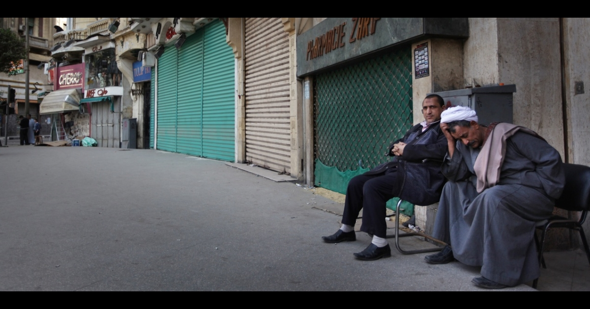 Egyptian men sit next to closed shops in Cairo, Egypt.</p>