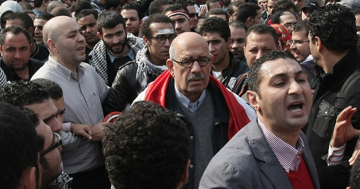 Mohamed ElBaradei (C), with a national flag around his shoulders, among thousands of protesters in Cairo's Tahrir Square on Nov. 25, 2011.</p>