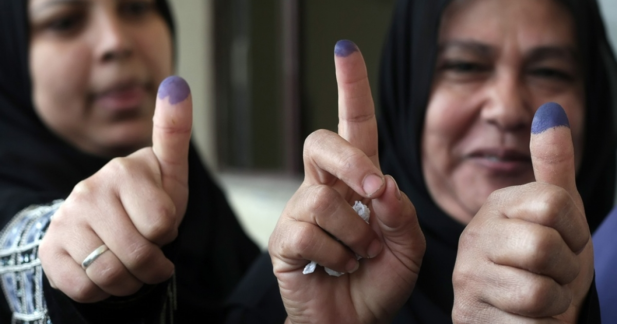 Egyptian women show their ink-stained fingers at a polling station in Cairo on Nov. 29, 2011.</p>