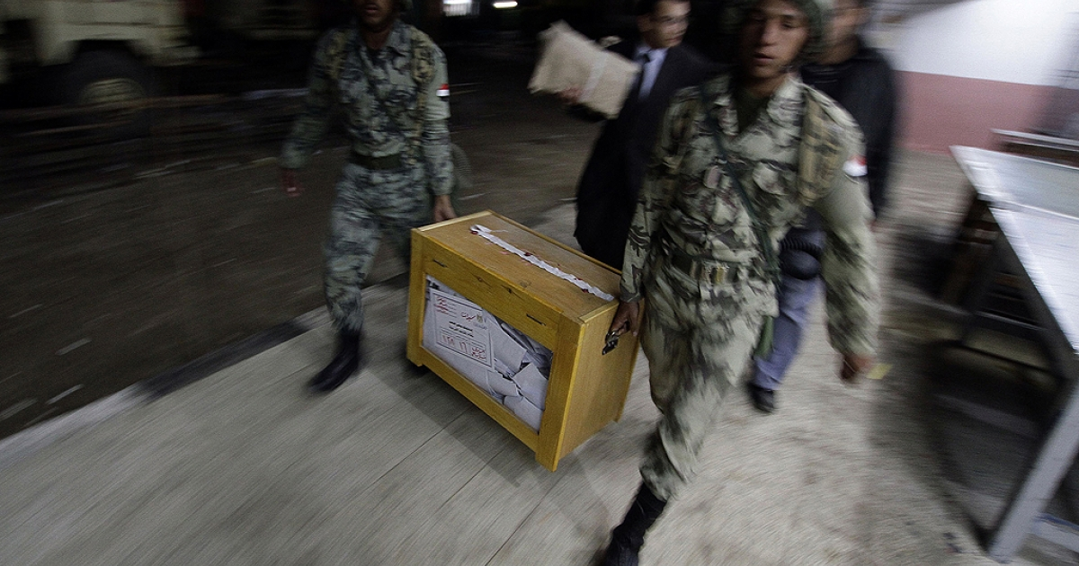 Egyptian soldiers carry a ballot box at the end of the first day of voting in Cairo's Shubra neighbourhood on November 28, 2011 before a second round of voting the following day.</p>