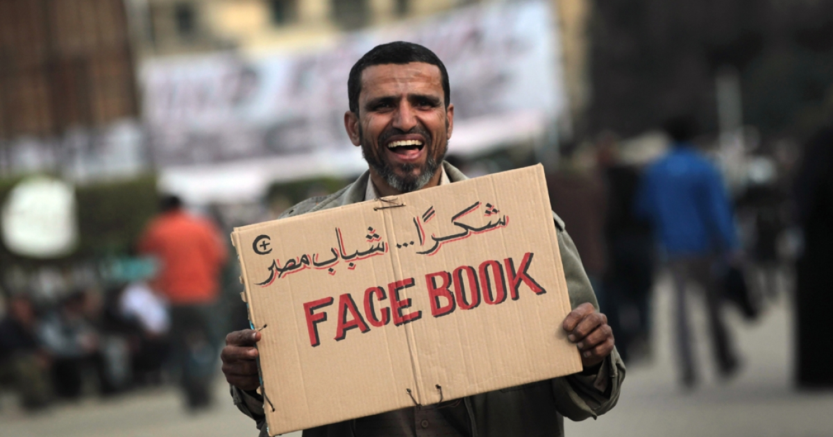 An anti-government demonstrator holds a sign during clashes on Feb. 3, 2011 in Cairo, Egypt.</p>