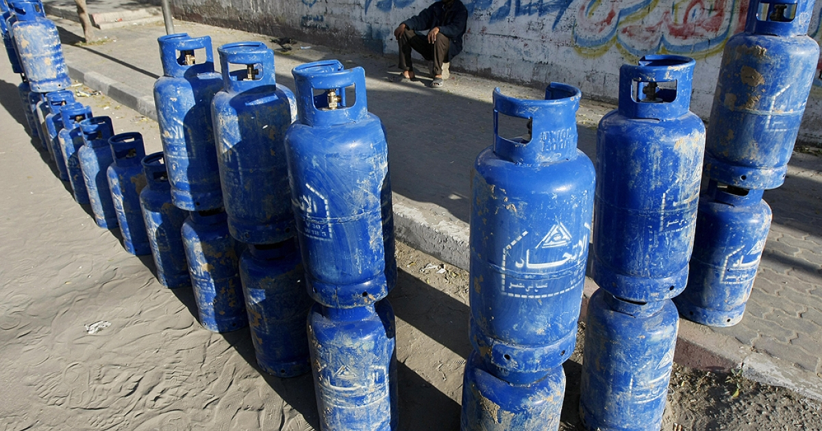 A Palestinian man sits with cylinders of cooking gas, smuggled into the Gaza Strip from Egypt through a tunnel, that he is selling on a street in Gaza city on December 6, 2008.</p>