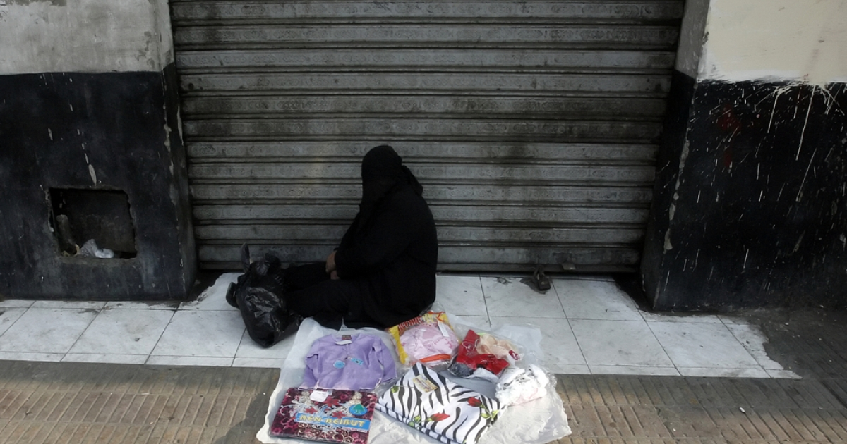 An Egyptian woman sells clothes on the side of a road in Cairo. Some 40 percent of Egyptians live on less than $2 per day, the World Bank says.</p>