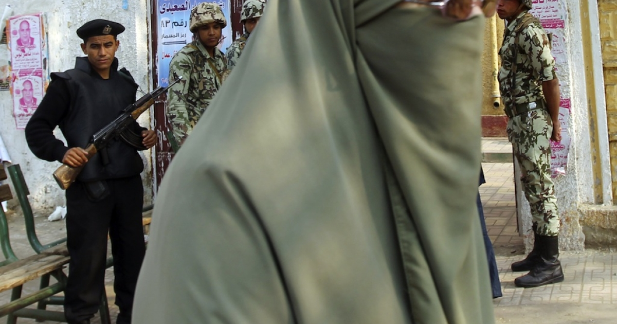 A woman wearing a full Islamic veil walks on front of Egyptian police and soldiers. Pro-Islamist students this week shut down a television production because the actresses were dressed indecently.</p>