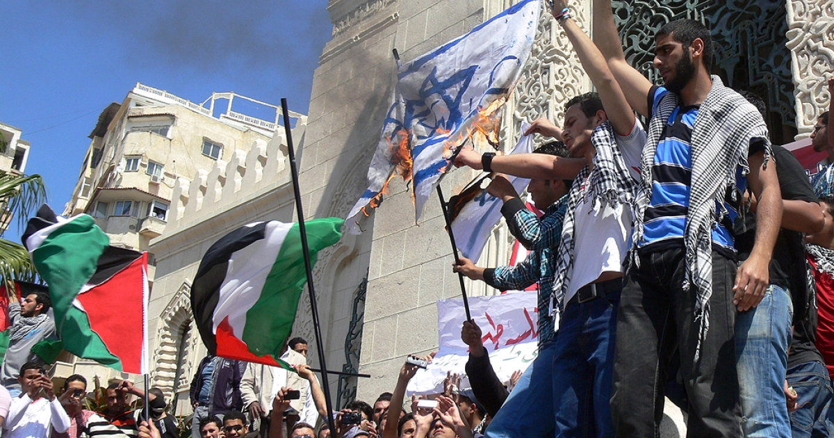 Protesters hold up the Palestinian flag as they burn the Israeli flag during a rally to mark the 1948 creation of the Jewish state known in Arabic as the