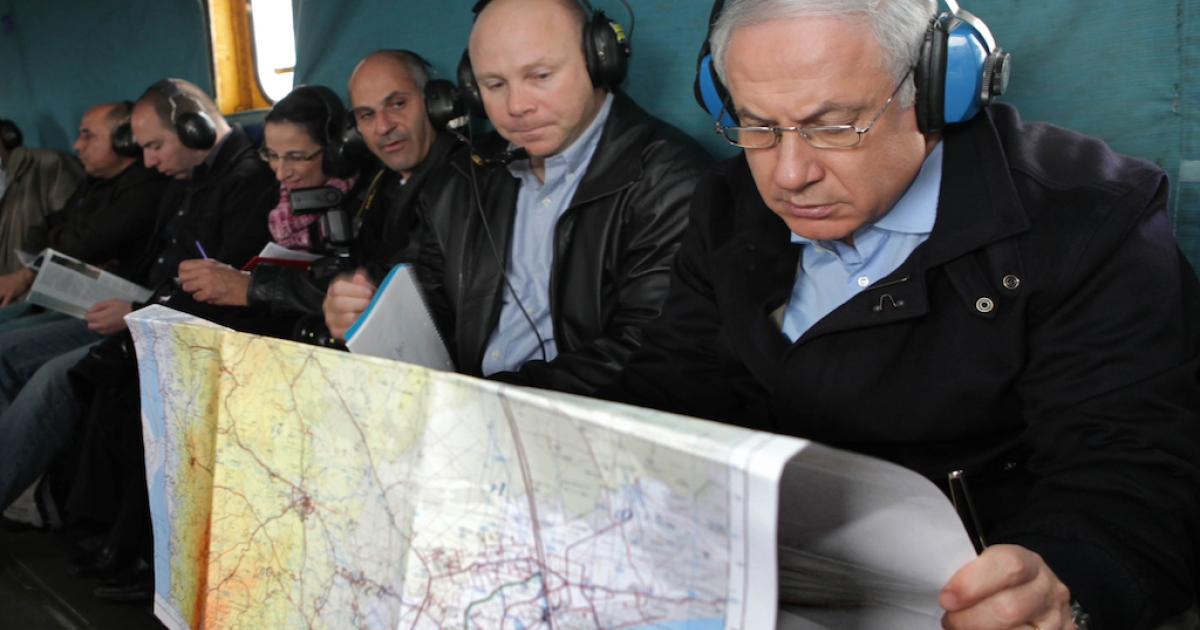 Israeli Prime Minister Benjamin Netanyahu (R) looks at a map of the Israel-Egypt border area during a flight in a military helicopter January 21, 2010 near the Egyptian border, in Israel. Judges investigating non-profits accused of receiving foreign funds in Egypt said one of the key pieces of evidence was the discovery of maps of Egypt inside the NGO offices.</p>