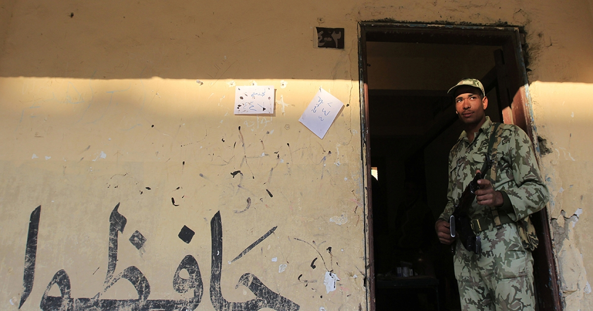 An Egyptian soldier stands guard at a polling station in a school during the run-off of the first round of voting at a polling station in Cairo on December 5, 2011. Islamist candidates looked to extend their crushing victory in Egypt's first parliamentary elections since the overthrow of president Hosni Mubarak.</p>