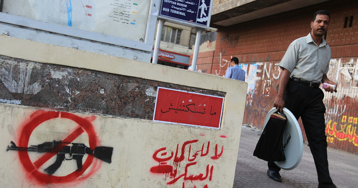An Egyptian man walks past an Arabic slogan that reads,