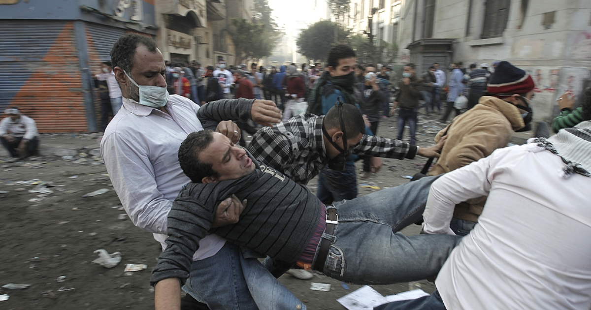 An Egyptian protester is carried away during clashes with riot police along a road which leads to the Interior Ministry, near Tahrir Square, in Cairo on November 23, 2011.  Several thousand Egyptians rallied in Tahrir Square demanding an end to military rule, despite a promise by the country's interim leader to transfer power to an elected president by mid-2012.</p>