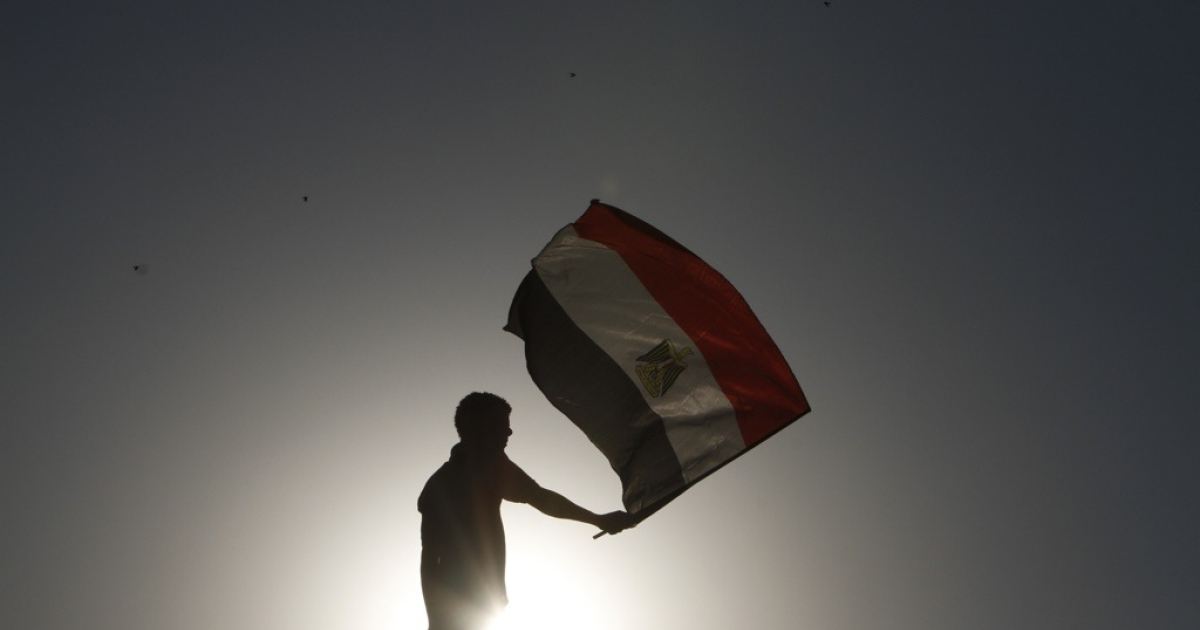 An Egyptian protester waves the national flag in Cairo's landmark Tahrir Square on June 5, 2012.</p>