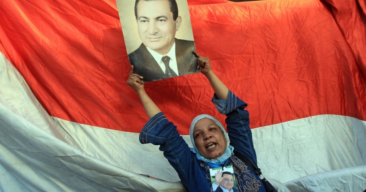 A supporter of ousted Egyptian President Hosni Mubarak holds his picture outside the Cairo police academy where Mubarak's trial is being held.</p>