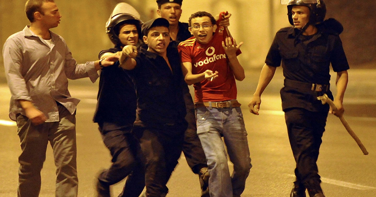 Egyptian riot police detain an Ahly football club supporter after clashes broke out between soccer fans and police after the team's Egyptian Cup match against Kima Aswan in Cairo overnight on September 7, 2011.</p>