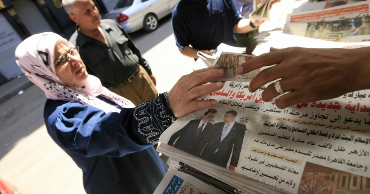 An Egyptian woman buys a newspaper featuring a front page picture of US President Barack Obama.</p>