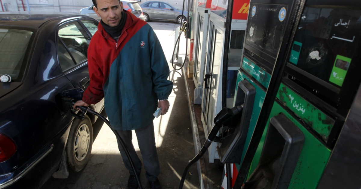 An Egyptian worker fills a customer's car tank at a petrol station in Cairo amid fears of an oil shortage.</p>