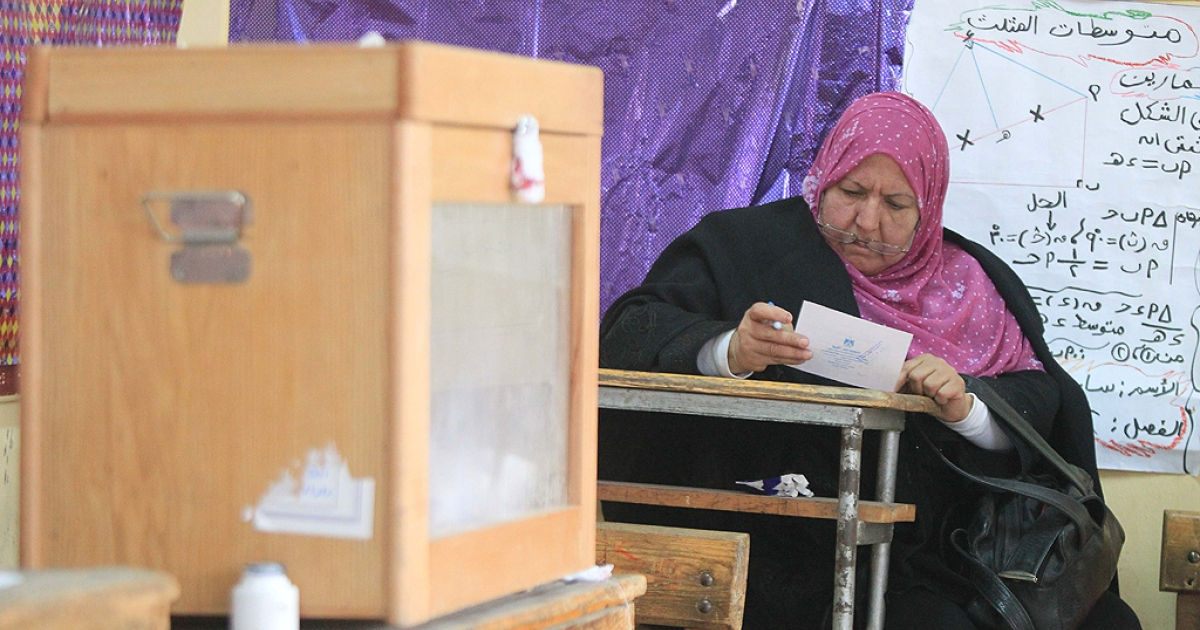 An Egyptian woman inspects her ballot during the vote on the second day of the run-off of the first round of voting at a polling station in Cairo on December 6, 2011.</p>