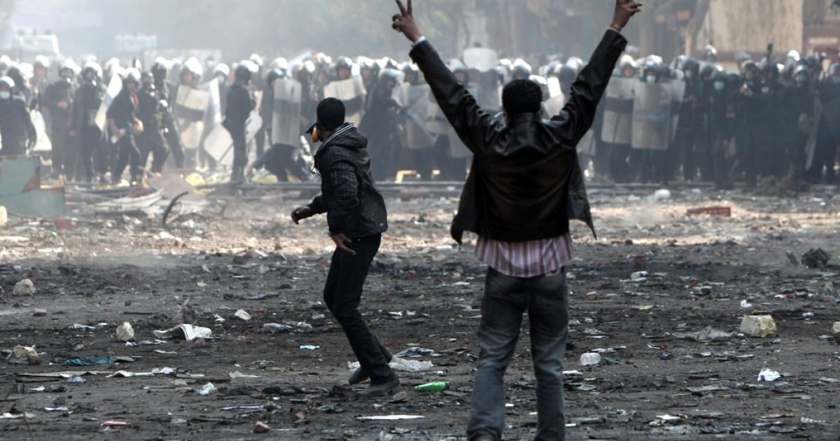 An Egyptian protester flashes the V-sign for victory during clashes with riot police along a road which leads to the Interior Ministry, near Tahrir Square, in Cairo on November 23, 2011.</p>