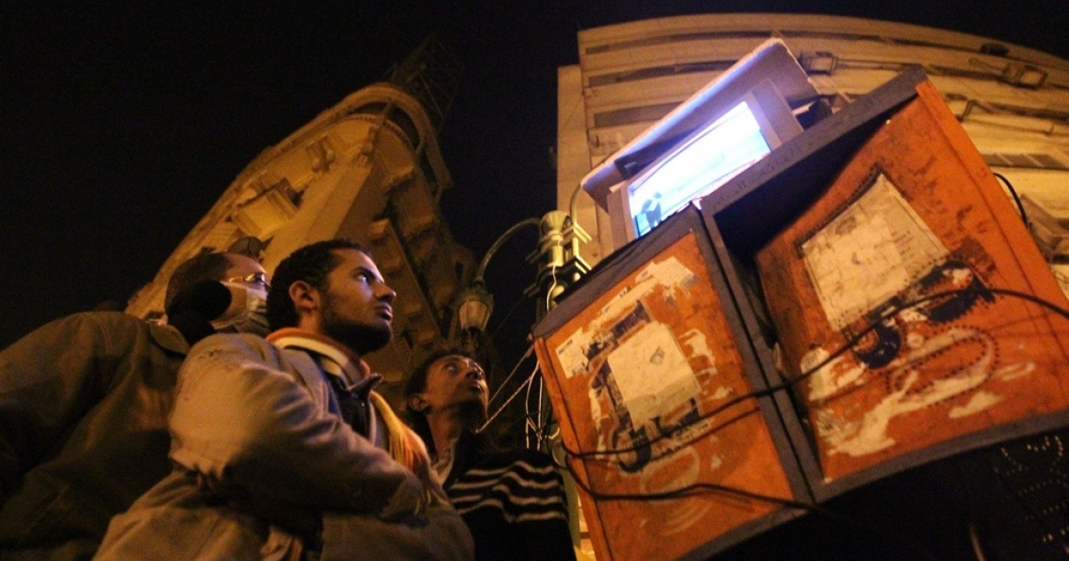 Egyptians gather to watch a television placed on top of public telephone booths in Cairo's Tahrir Square.</p>