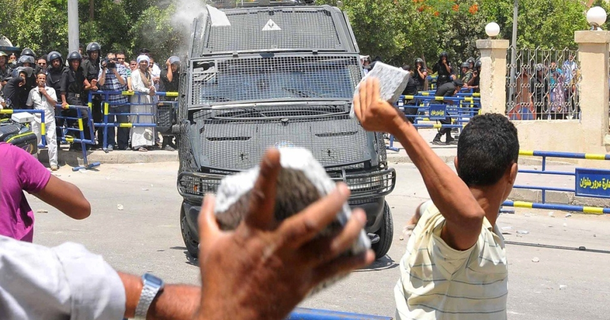 Egyptians throw stones at a police convoy carrying ex-interior minister Habib Adli outside a court in Cairo on June 26, 2011 as hundreds of Egyptians angry with the delays in his trial clashed with anti-riot police.</p>