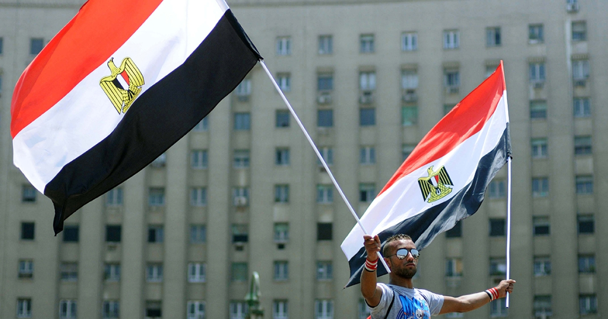 An Egyptian man waves two national flags during a protest in Cairo's Tahrir Square July 11, 2011, vowing to keep up their sit-in which began on July 8, despite a series of concessions by the Egyptian prime minister.</p>