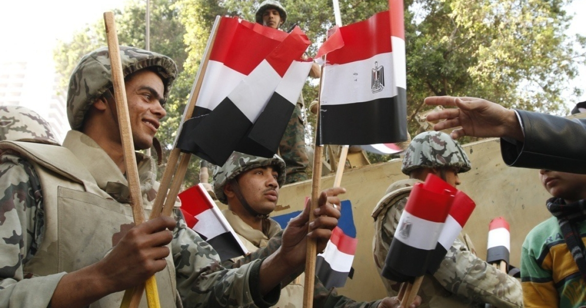 Egyptian army troops distribute national flags in Cairo's landmark Tahrir Square as hundreds of thousands of protesters gathered on February 18, 2011 to celebrate the nationwide revolt which forced president Hosni Mubarak to step down and hand over power to a military junta a week earlier.</p>