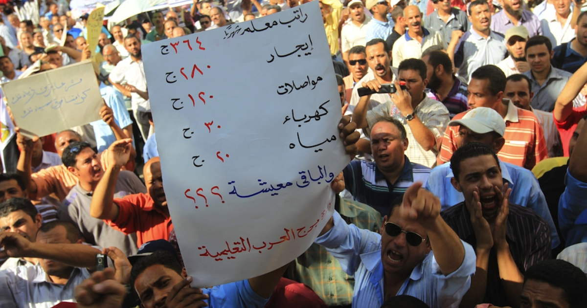 Holding up a sign listing the cost of living, thousands of the Egyptians teachers protest during a strike in front of the Prime Minister's office in downtown Cairo in Sep. 2011. Tomorrow, dozens of groups and universities will begin an open strike against the military-run government.</p>