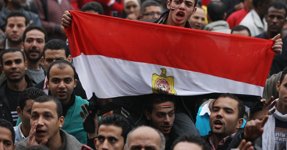 A man holds Egypt's flag in Tahrir Square as people gather for the first anniversary of the revolution on Jan. 25 in Cairo, Egypt.</p>