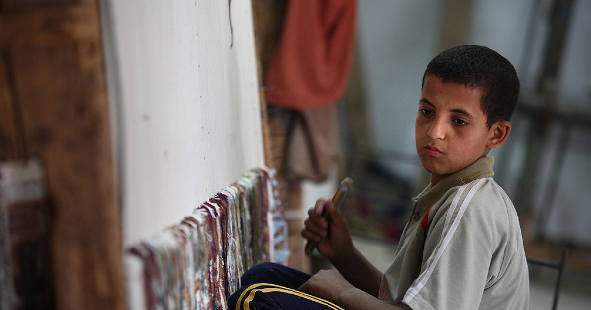 Bedouin boy Ramadan, aged 14, weaves a carpet at a government run carpet school on May 28, 2011 in Sakara, Egypt.</p>