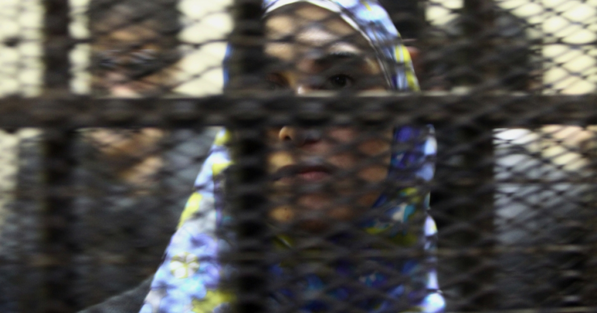 One of fourteen Egyptian activists who worked in Egypt with civil society groups stands inside a cage during their trial in Cairo Sunday.</p>
