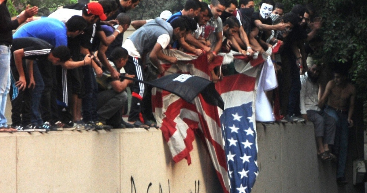 Egyptian protesters tear down the US flag at the US embassy in Cairo on Sept. 11, 2012.</p>